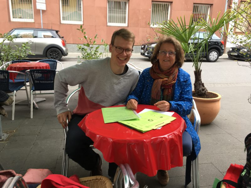 Konstantin Werner und Irmgard Münch-Weinmann sitzen gemeinsam an einem Tisch in einem Cafe. Vor ihnen liegen Dokumente. Sie lächeln in die Kamera.